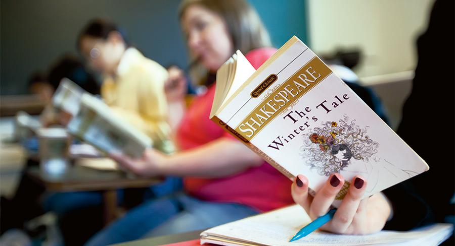 Wellesley College student reads a copy of The Winter's tale by Shakespeare in a classroom