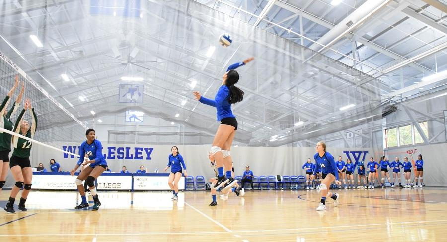 Wellesley College volleyball team player hits a volleyball across the net to the opposing team