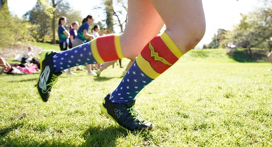 A Wellesley College student with cleats and Wonder Woman stockings on runs across a green playing field