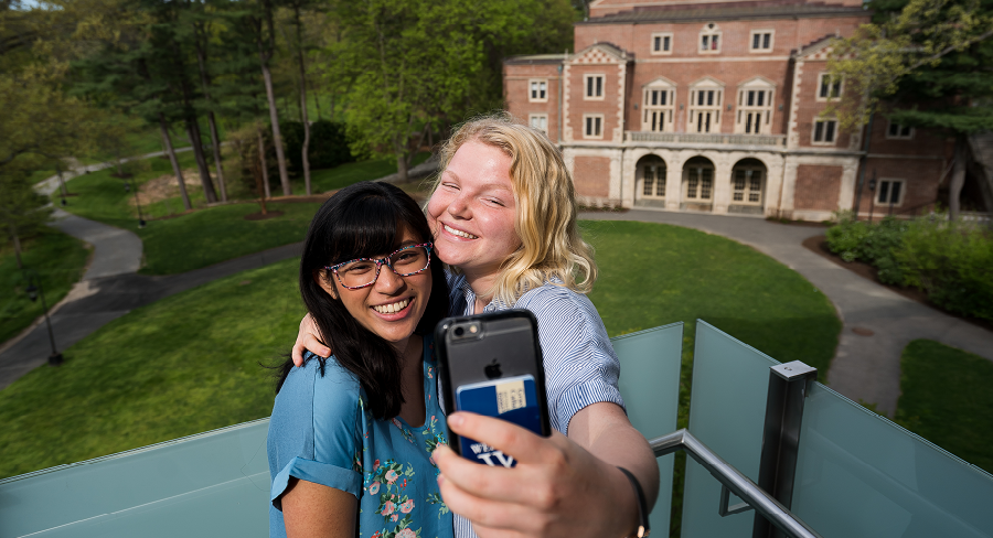 Two Wellesley College students take a selfie in front of Diana Champman Walsh Alumnae Hall