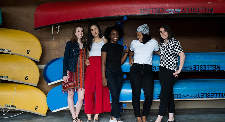 Five Wellesley College students pose for a photo in front of blue canoes in a boat house