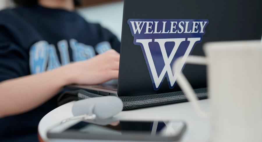 A student types on a laptop with the Wellesley College logo sticker on the front