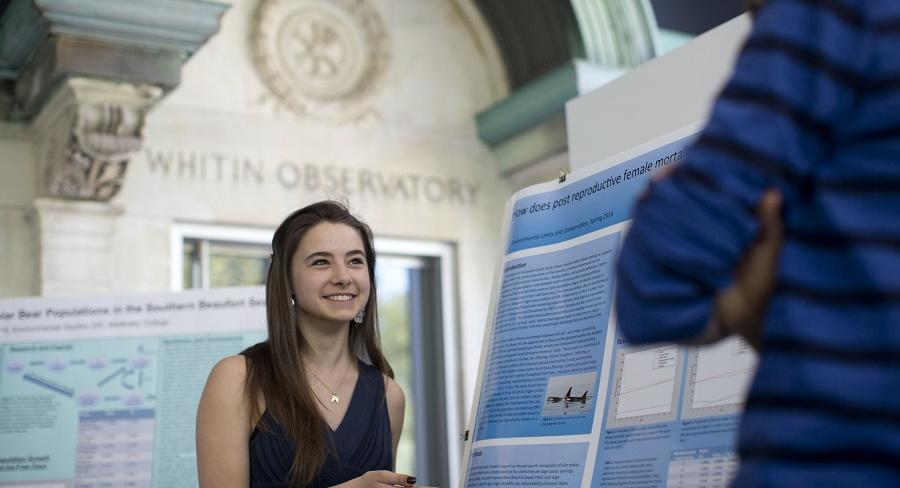 Wellesley College student stands next to her research poster