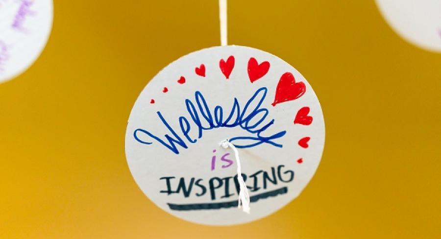 "A still photo of a button adorned with hearts that reads ""Wellesley is Inspiring"""