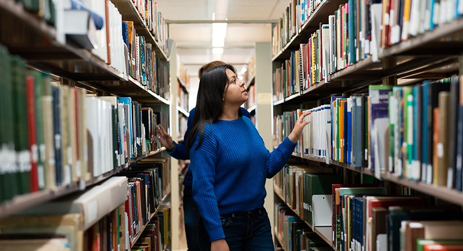 Two students browse for books in the Wellesley College Clapp Library
