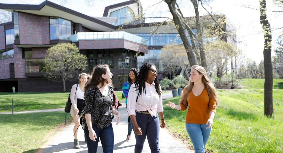 A group of Wellesley College students walk with the Lulu Chow Wang Campus Center in the background