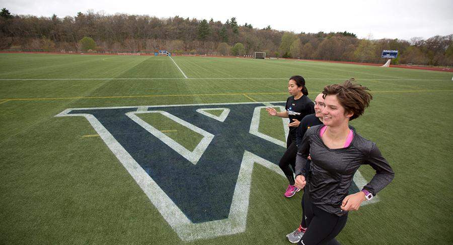 Wellesley student athletes run on a sports field with the Wellesley logo