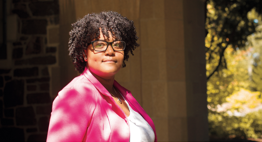 Wellesley College alumna, Serenity Hughes, smiles for a portrait, wearing a pink blazer