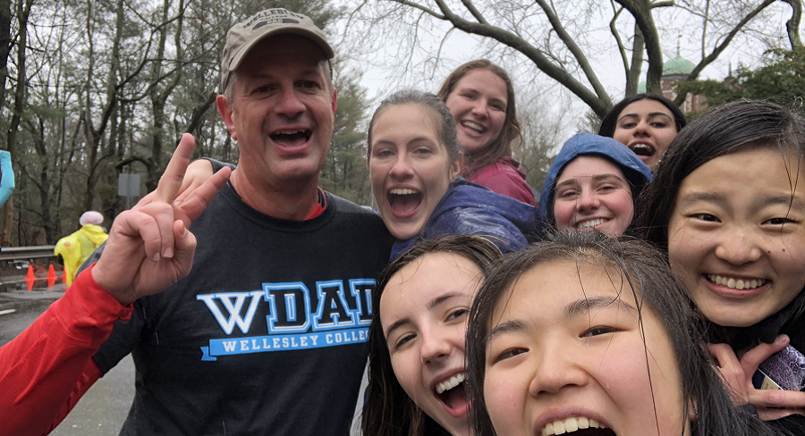 Wellesley College student, Lilly Armstrong, and a group of friends, pose fora  photo cheering on Lilly's dad who is running the Boston Marathon