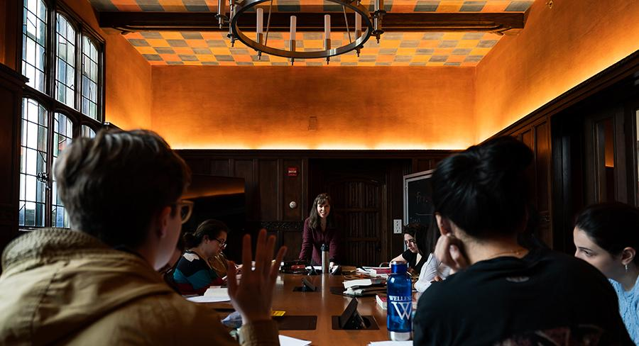 A Wellesley College student raises her hand in a seminar class while professor looks on