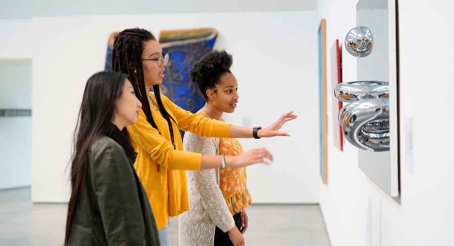 A Wellesley College student leads a tour of two other students through the Davis Museum, explaining an art installation