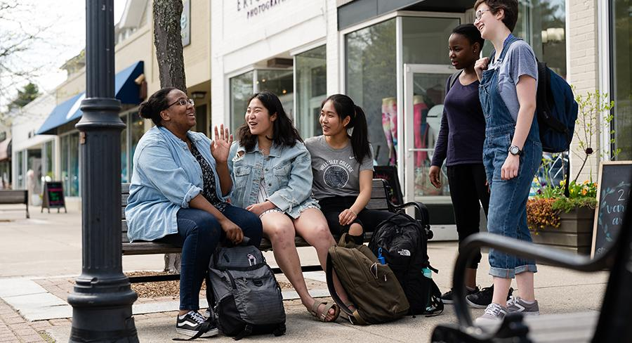Four college students laugh on a bench in downtown Wellesley